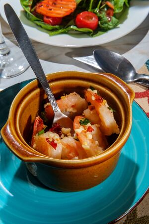 Portuguese gambas al ajillo garlic shrimp in terracotta cazuela de barro bowl Stock Photo