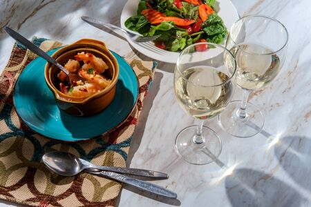 Romantic Portuguese gambas al ajillo garlic shrimp dinner in terracotta cazuela de barro bowl with two glasses of pinot grigio white wine