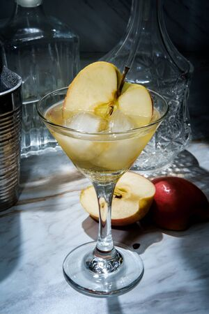 Gin appletini cocktail in martini glass with ice and sliced apple garnish