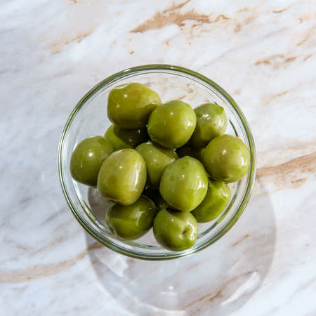 Nocellara del Belice or castelvetrano olives in glass bowl on marble kitchen table