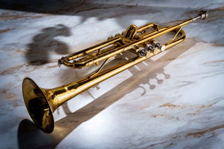 Rusty old dented classical trumpet on marble table