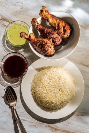 Indian appetizer tandoori chicken legs with creamy mint and plum chutneys with side dish of basmati rice