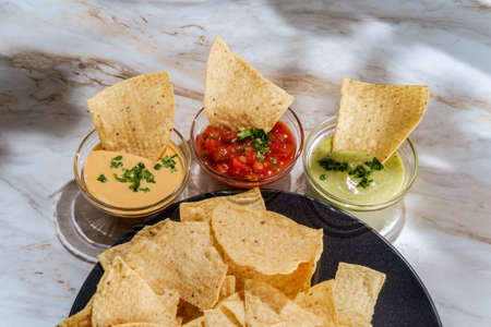 Tortilla chips tomato and guacamole salsa with queso Mexican cheese dip on marble kitchen table