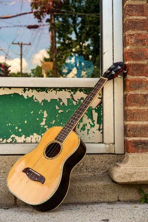 Acoustic baritone ukulele guitar leaning against storfront window