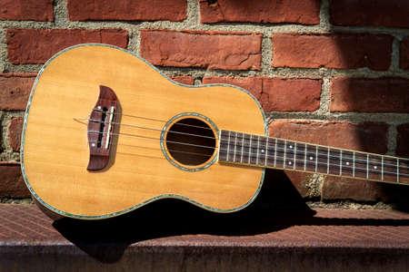 Acoustic baritone ukulele guitar left outside performance venue againts brick wall Stock fotó