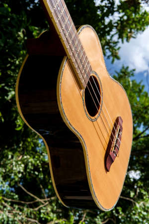 Acoustic baritone ukulele guitar held up to bright blue sky with fluffy clouds