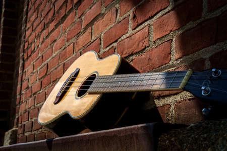 Acoustic baritone ukulele guitar left outside performance venue againts brick wall