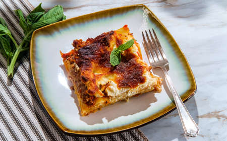 Home made Italian baked cheese and meat lasagna on marble kitchen table