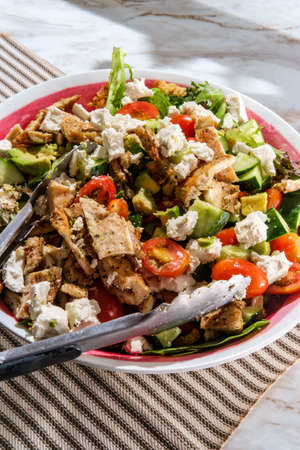Big chicken salad serving bowl with feta cheese and avocado
