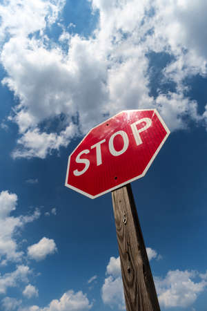 Stop sign with bright blue sky with fluffy clouds