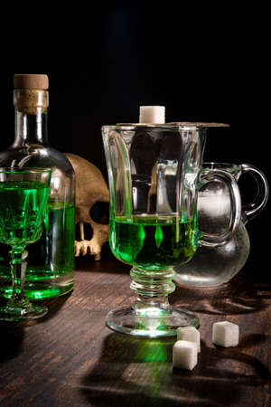 Green absinthe liquor in glass with ice water to pour over sugar cube
