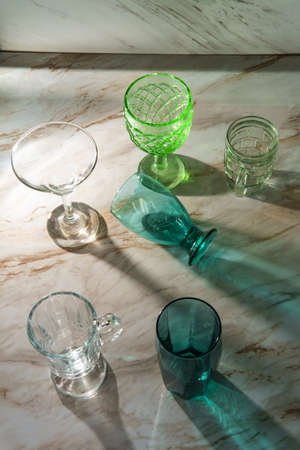 Various shaped drinking glasses on marble kitchen table