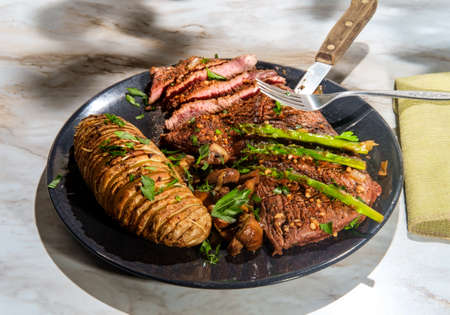 Sirloin tip steak with potato a la hasselbacken mushrooms and asparagus Standard-Bild