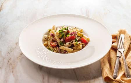 Italian pesto pasta salad with pearl mozzarella cheese balls and halved cherry tomatoes Archivio Fotografico