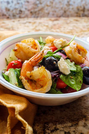 Fresh Greek salad with grilled shrimp and feta cheese with balsamic vinaigrette dressing