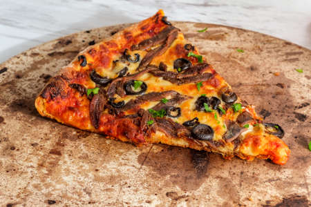 New York style slice of pizza with anchovies and black olives