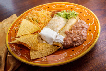 Authentic Mexican burrito and taquito dinner with rice and refried pinto beans Stock Photo