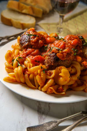 Spaghetti and meatballs with trottole noodles and chopped fresh basil