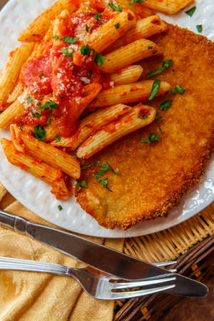 German chicken schnitzel with penne in red tomato sauce