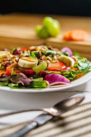 Summer organic fruit salad with bananas strawberries grapes and balsamic vinaigrette Foto de archivo