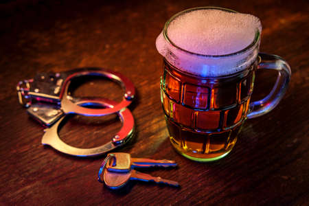 Mug of frothy beer with handcuffs and keys symbolizing drunk driving arrest