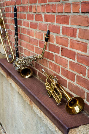 Musical instruments including trombone trumpet clarinet and saxophone on brick wall outside Jazz club 写真素材