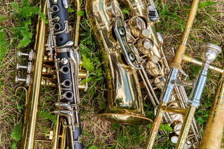 Musical instruments including trombone trumpet clarinet and saxophone lay in grassy field at music festival