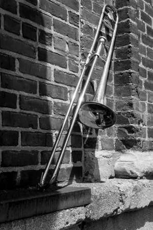 Old rusty vintage trombone leans against brick building outside jazz club