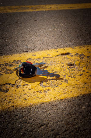 Lost car keys on distressed road painted yellow lines
