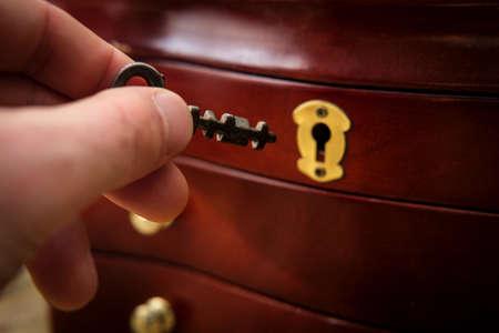 Old antique skeleton key on distressed textured wooden background