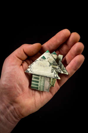 Hand holds origami paper money house for real estate and housing market concept