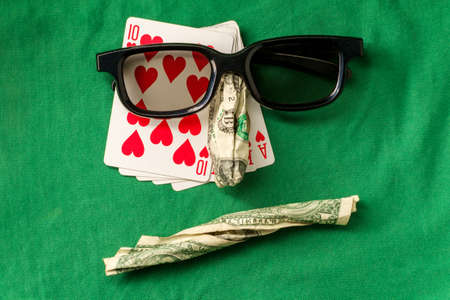Silly bad poker face metaphor made from various gambling items including money and cards Archivio Fotografico