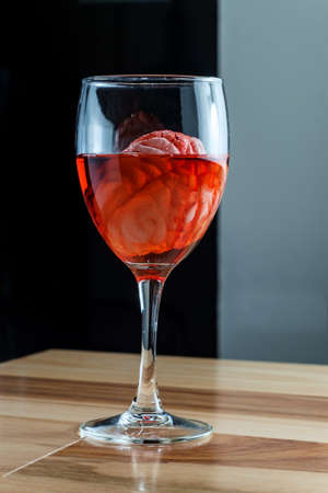 Human brain in red wine glass soaking for alcoholism addiction concept