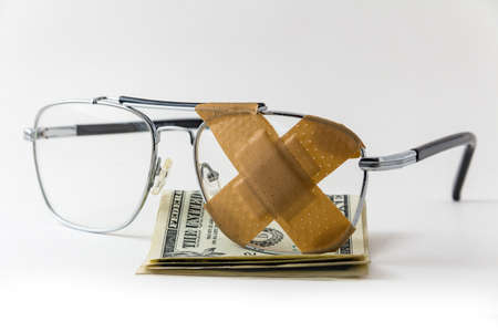 Eye glasses with band-aid X and dollar bills - healthcare is expensive