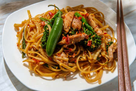 Pad kee mao otherwise known as drunken noodles is a spicy Thai stir-fried noodle dish with thinly sliced chicken thighs and chinese broccoli