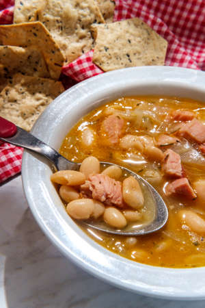 Simple slow-cooker ham and cannellini bean soup with multigrain hexagon crackers for dipping