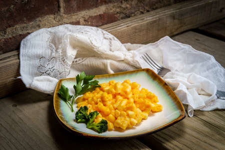 Delicious macaroni and cheese on wooden table with dramatic dark and moody lighting