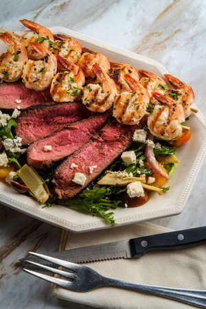 Blue cheese surf and turf shrimp and steak salad cooked rare with kalamata olives and artichoke hearts Reklamní fotografie