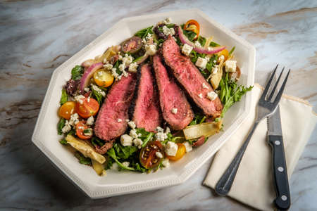 Blue cheese steak salad cooked rare with kalamata olives and artichoke hearts