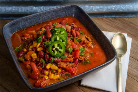 Chorizo sausage chili con carne dinner garnished with sliced jalapeno