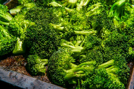 Broccoli florets on baking pan seasoned with salt pepper and olive oil