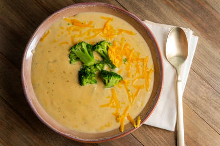 Rustic hearty broccoli and cheddar cheese soup on wooden kitchen table Reklamní fotografie