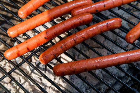 Grilling foot long hotdogs for summer barbecue picnic