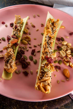 Healthy snack peanut butter celery or ants on a log with mixed nuts and seeds Foto de archivo