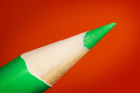 Green pencil over red background