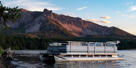 A pontoon boat tied to the shoreline at sunset Paulina Lake Paulina Peak