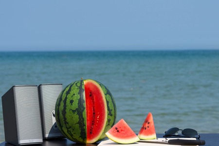 Pair of speakers, whole and cut watermelon with knife and wooden cutting board and a pair of sunglasses on the beach in summer ready for summer party.