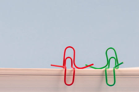 Paper clips red and green sitting on a white paper ream and talking or having a conversation. A photo with a copy space. Two paper clips who are friends talking or having a conversation or friendly talk. Ideal for back to school or office works. Banque d'images - 109930153