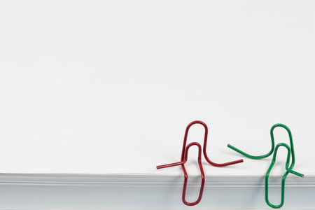 Paper clips red and green sitting on a white paper ream and talking or having a conversation. A photo with a copy space. Two paper clips who are friends talking or having a conversation or friendly talk. Ideal for back to school or office works. Banque d'images - 109930155