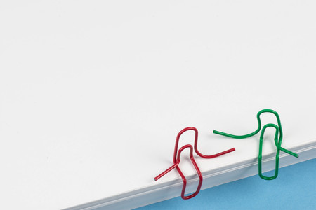 Paper clips red and green sitting on a white paper ream and talking or having a conversation. A photo with a copy space. Two paper clips who are friends talking or having a conversation or friendly talk. Ideal for back to school or office works. Banque d'images - 109930156